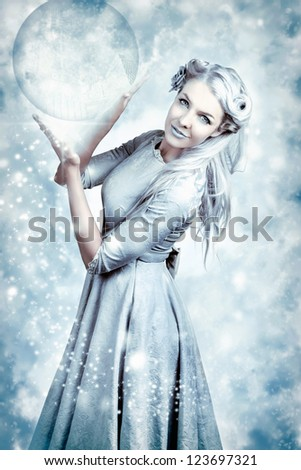 Magic Winter Girl Wearing Luxury Fashion And Elegant Hairstyle With Beautiful Make-up Holding Crystal Ball In Falling Snow