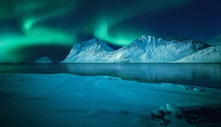 Magical aurora borealis above frozen sea coast and snow covered mountains reflected in the ocean in winter season. Amazing Norway nature seascape. Famouse travel locations. Scenic Image of Norway