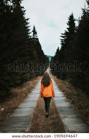 Magical brunette aged 20-24 in a glowing orange sweatshirt on the road in the Jizera forests. Hiker is looking to the future. Stepping forward. Make an important decision. Foto stock ©