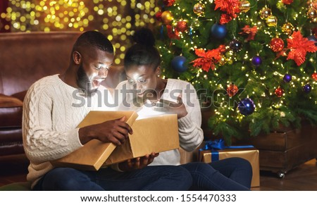 Magical Christmas. Excited african american couple opening xmas gift box in living room near Christmas tree, celebrating holidays at home, panorama Photo stock ©