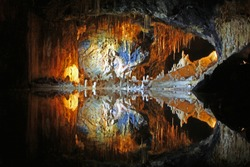 Magical colorful cave with underground lake framed with stalagmites and stalactites in former alum shale mine in Thuringia, Germany. A place from fairy tales. Mirror reflection in the water.