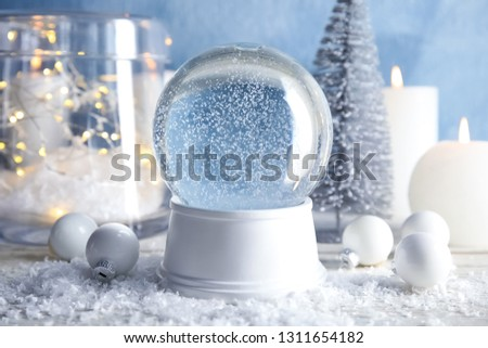 Magical empty snow globe with Christmas decorations and candles on table