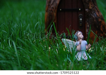 Magical fairy statue garden outside with vibrant green grass and delicate sweet fairy. Magical wooden fairy door leads to a fairy tale land.