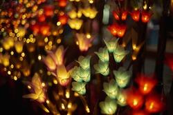 Magical fairy-tale garland of flower-shape lights, at Chiang Mai, Thailand, night bazaar.