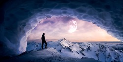 Magical Fantasy Adventure Composite of Man Hiking in an Ice Cave with Winter Mountain Landscape. Colorful Sunset Sky Art Render. Background taken from British Columbia, Canada.