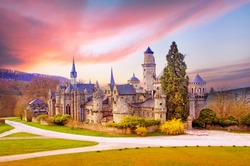 Magical landscape with medieval Lion castle or Lowenburg in Wilhelmshoehe Castle Park in Kassel, Germany, Europe at dawn.