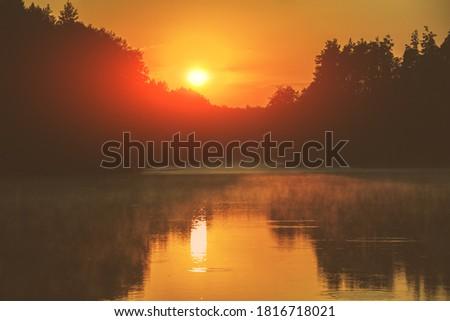 Photo of  Magical orange sunset over lake. Serene lake in the evening. Nature landscape