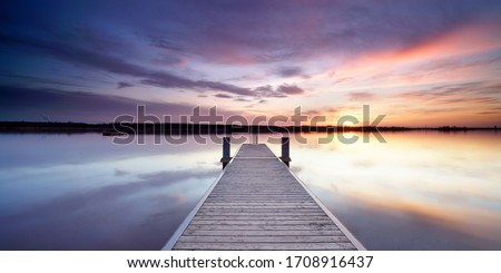 Photo of  magical place at the lake, romantic evening on wooden jetty at the beach