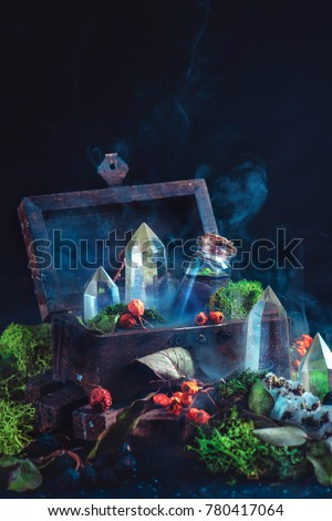 Magical still life with a wooden chest, potion bottle, crystals, moss, berries and leaves on a dark background. Modern witchcraft concept with copy space. #780417064