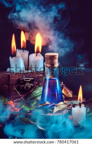 Magical still life with spells, herbs, potion ingredients, wax candles and a glass bottle with mystic liquid on a dark background. Modern witchcraft concept with copy space. #780417061