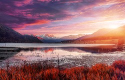 Magical Sunset Over the Mountains lake. Colorful sky under sunlit reflected in water. Awesome alpine highlands in sunny day. Picture of wild area. Wonderful Natural Background, view with Dramatic sky