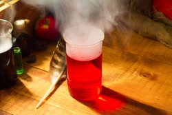 Magical witch lab with fog or smoke and red potion for Halloween wooden background