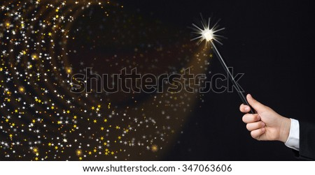 Magician hand conjuring sparks on black background - copy space with magic