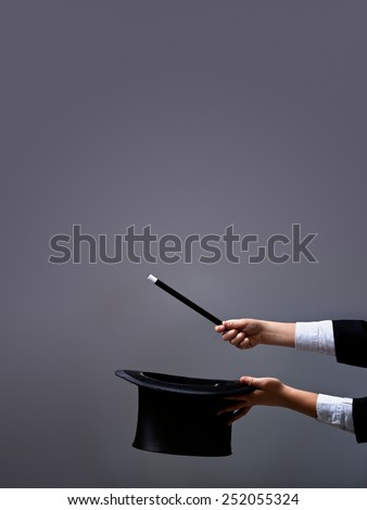 Magician hands holding hat and magic wand on gray background - with lots of copy space