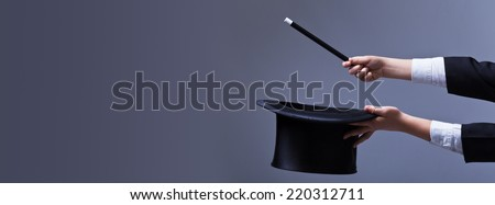 Magician hands with hat and magic wand - with copy space