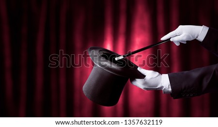 magician holding a top hat and magic wand with a red curtain as background #1357632119
