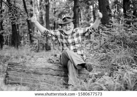 Magician in forest. Woodman magician concept. Folk magic. Mature man with beard in hat. Wise old man. Herbal remedies. Freak healer. Supernatural or superstitious. Person purported magical abilities.