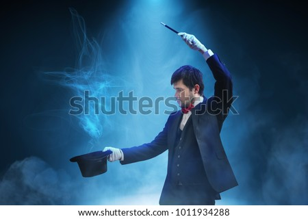 Magician or illusionist is showing magic trick. Blue stage light in background. #1011934288