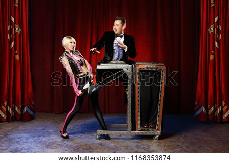 Magician performs magic trick, woman saw up with a chainsaw a man