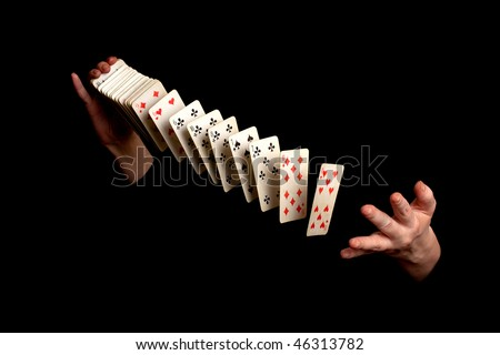 magician showing his trick with cards on black background