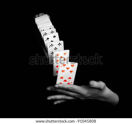 magician showing his trick with deck of cards on black background
