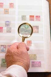 Maginfying glass held in a hand to  view stamp in a philatelic collection