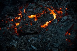 Magma textured molten rock surface. Lava flame on black ash background. Danger, hazard, energy concept. Volcano, fire, crust. Formation, geology, nature, environment.