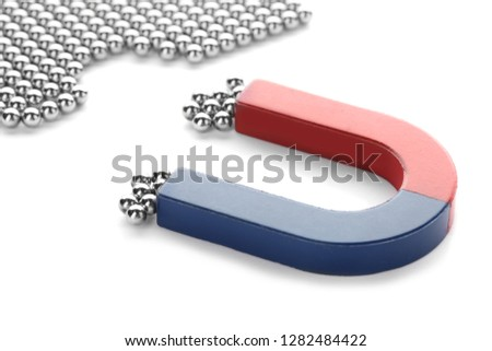 Magnet attracting chrome balls on white background. Business leadership concept #1282484422