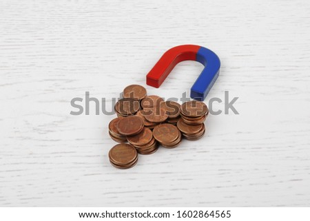 Magnet attracting coins on white wooden table