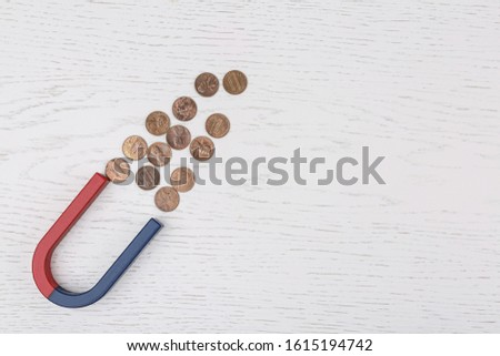 Magnet attracting coins on white wooden table, flat lay. Space for text