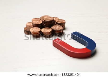 Magnet attracting coins on wooden background. Business concept #1323351404