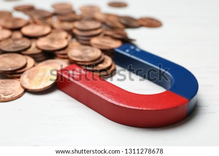 Magnet attracting coins on wooden background, closeup. Business concept #1311278678
