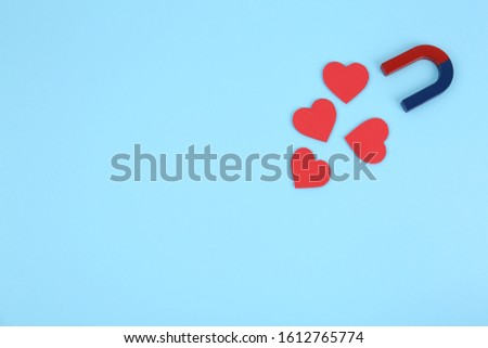 Magnet attracting hearts on light blue background, flat lay. Space for text