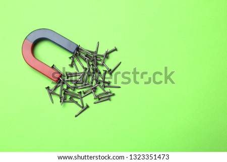 Magnet attracting nails on color background, top view with space for text #1323351473