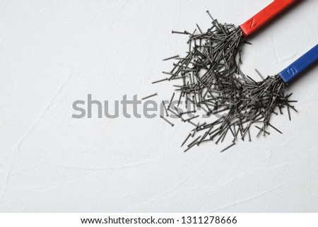 Magnet attracting nails on light background, top view with space for text #1311278666