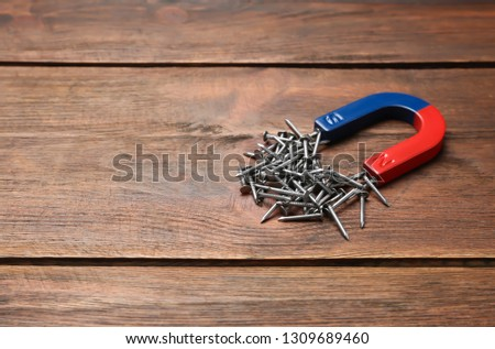 Magnet attracting nails on wooden background, space for text #1309689460