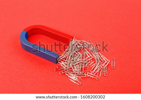 Magnet attracting paper clips on red background