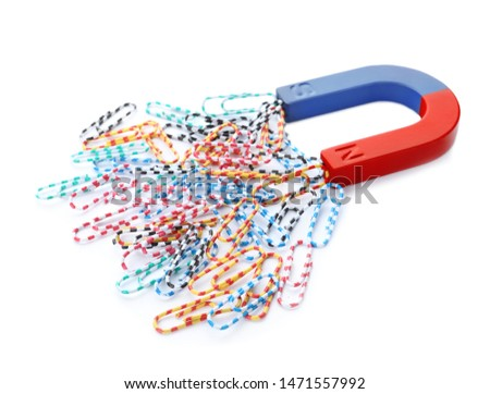 Magnet attracting paper clips on white background #1471557992