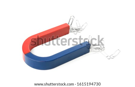 Magnet attracting paper clips on white background