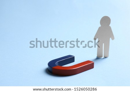 Magnet attracting paper person on light blue background, space for text #1526050286