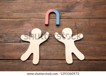 Magnet attracting people traffic on wooden background, top view. Marketing concept #1293360973