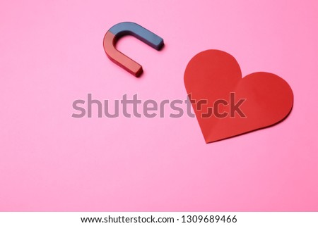 Magnet attracting red heart on color background, top view with space for text. Love concept #1309689466