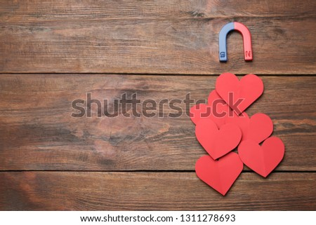 Magnet attracting red hearts on wooden background, top view with space for text. Love concept #1311278693