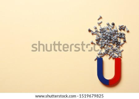 Magnet attracting screws on beige background, flat lay. Space for text