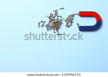 Magnet attracting screws on light blue background, flat lay. Space for text #1539986123