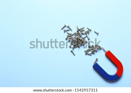Magnet attracting screws on light blue background, flat lay. Space for text #1542957311