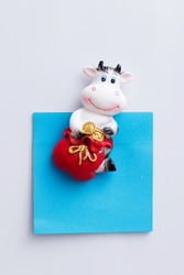 Magnet on the refrigerator in the form of a bull, a cow-a symbol of the New year and Christmas 2021. The blue sticker is for your records.