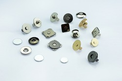 Magnetic buttons for making wallets and backpacks. Magnetic button for fastening leather goods. Different types and colors of metal buttons on a white background. Sewing accessories for clothes.