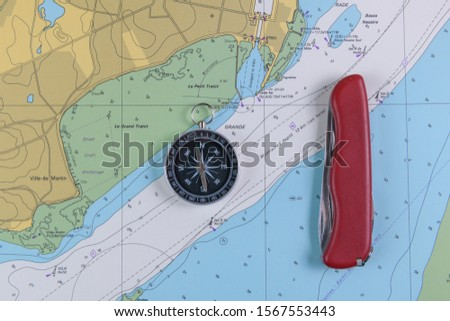 Magnetic compass and folding knife on a nautical navigational map