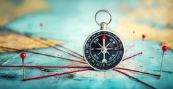 Magnetic compass  and location marking with a pin on routes on world map. Adventure, discovery, navigation, communication, logistics, geography, transport and travel concept background.. Macro photo.